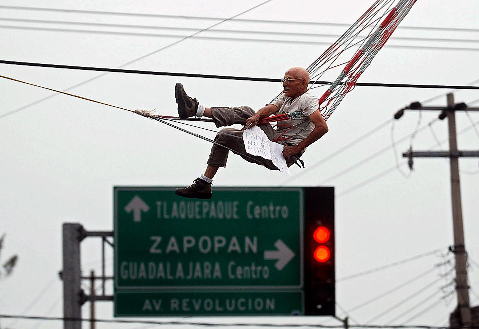 14) Висящий в гамаке мужчина протестует против новой автобусной линии в мексиканском городе Гвадалахара. (Ivan Garcia/Agence France-Presse/Getty Images)