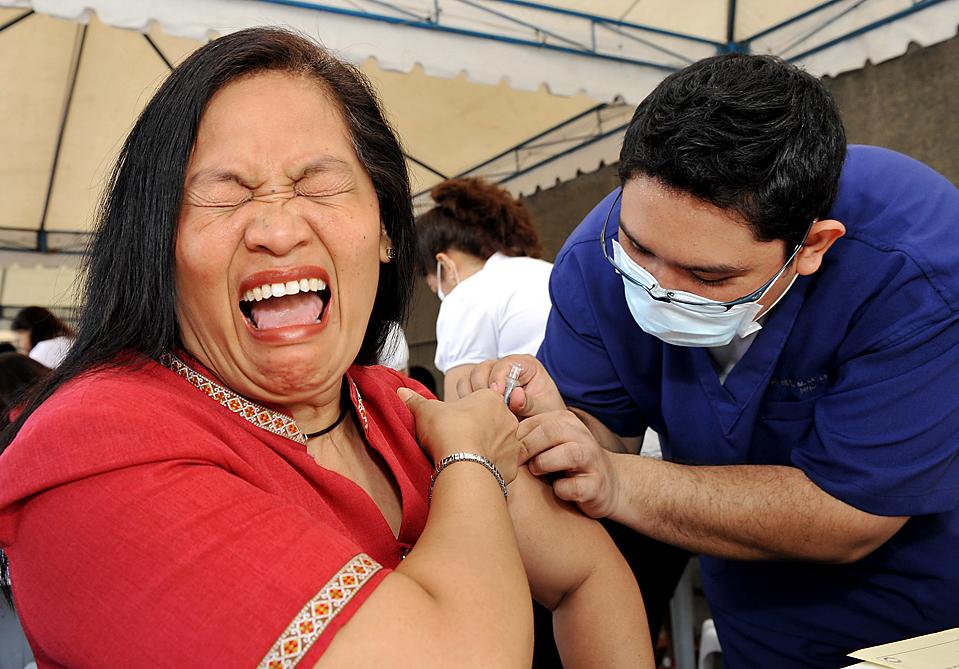 15) Медик делает прививку от гриппа госслужащей из филиппинской столицы Манила. Правительство Филиппин подтвердила вспышку гриппа A/H1N1 в сельской местности на севере страны, где болезнь была диагностирована у 20-и человек. Всего на Филиппинах зафиксировано более 200 случаев заражения гриппом A/H1N1. (Ted Aljibe/Agence France-Presse/Getty Images)