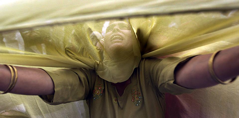 Кашмирская мусульманка простирает руки к верховному священнику во время демонстрации реликвии, представлющей собой волос из бороды пророка Мухаммеда. Церемония проводилась в честь годовщины со дня смерти первого Калифа Ислама в усыпальнице Хазратбал, расположенном в индийском городе Сринагар. (Dar Yasin/Associated Press)