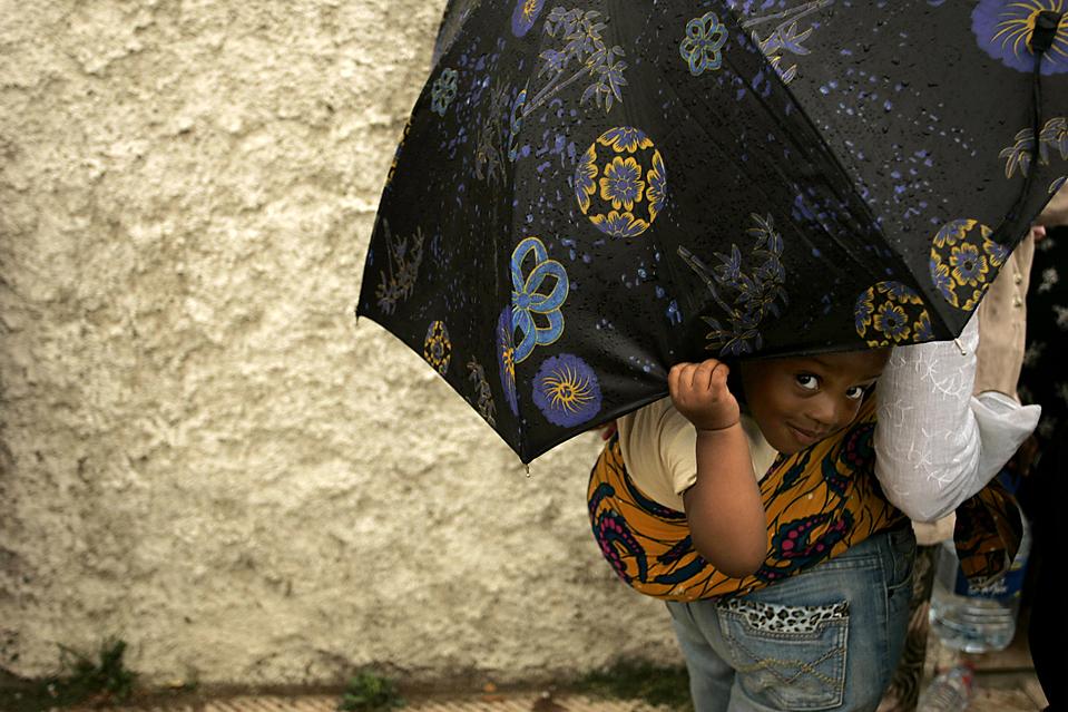 Ребенок выглядывает из-под зонта во время акции протеста в марокканском городе Рабат. Более сотни африканских беженцев устроили сидячую забастовку перед верховной комиссией по делам беженцев в марокканской столице, требуя выдать им визы в Европу. (Rafael Marchante/Reuters)