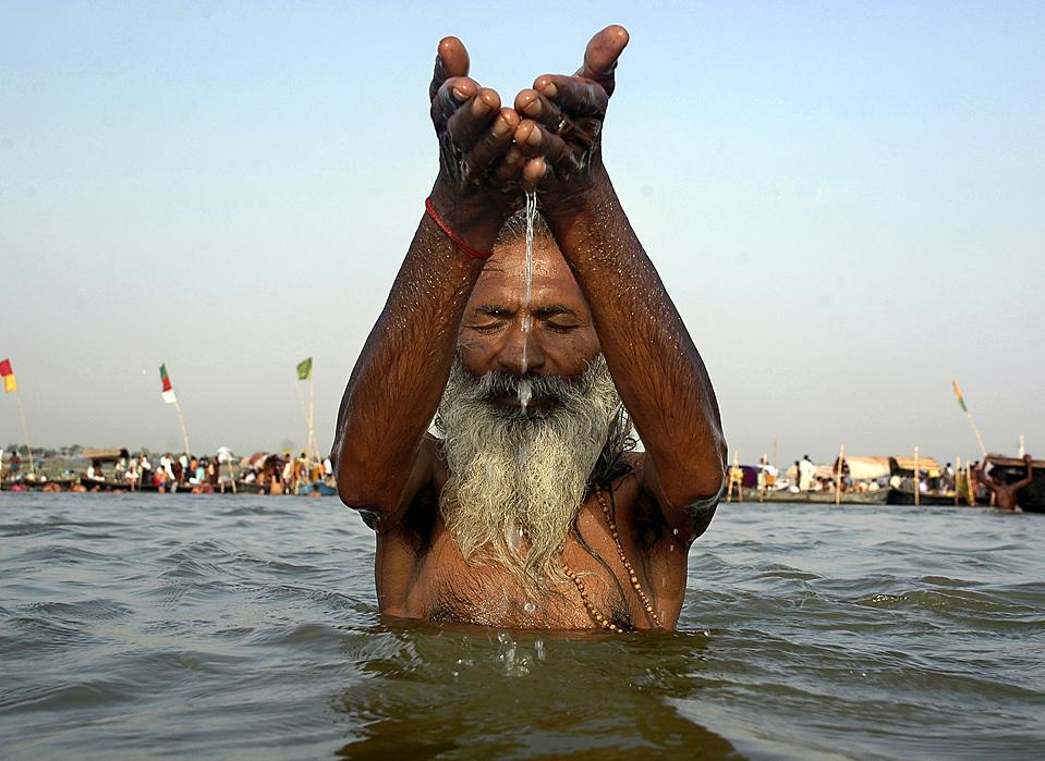 Садху, индусский праведник возносит молитвы солнцу окунувшись в воды Ганги в индийском городе Аллахабад. Аллахабад расположен в месте слияния рек Ганги, Ямуны и мифической реки Сарасвати и является одним из центров индуизма. (Rajesh Kumar Singh/Associated Press)