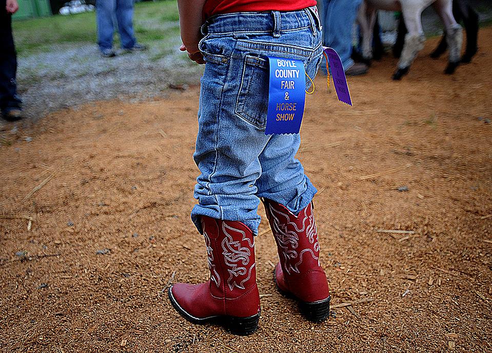 Анна Кейт Мерфи демонстрирует призовые ленты, которые ее овечка выиграла во время Ярмарки графства Боил в Данвилле. (Clay Jackson/Associated Press)