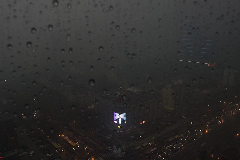 Из окна здания в деловом центре Пекина сквозь завесу дождя виден экран, на котором президент Китая Ху Дзинь Тао говорит речь. Фото сделано во вторник в обеденное время. В Международном аэропорту Пекина из-за грозы были незначительно задержаны рейсы. (Alexander F. Yuan/Associated Press)
