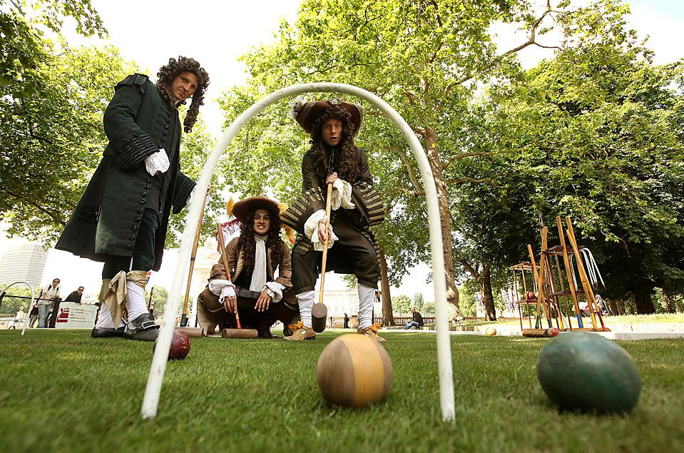 На знаменитой лондонской улице Пэлл Мэлл люди, одетые в костюмы 17-ого века, играют в игру «Paille Maille». Эта игра существует уже 400 лет и была необычайно популярна в 17 веке. Впервые в нее начали играть именно на этой улице, откуда и пошло ее название. (Oli Scarff/Getty Images)