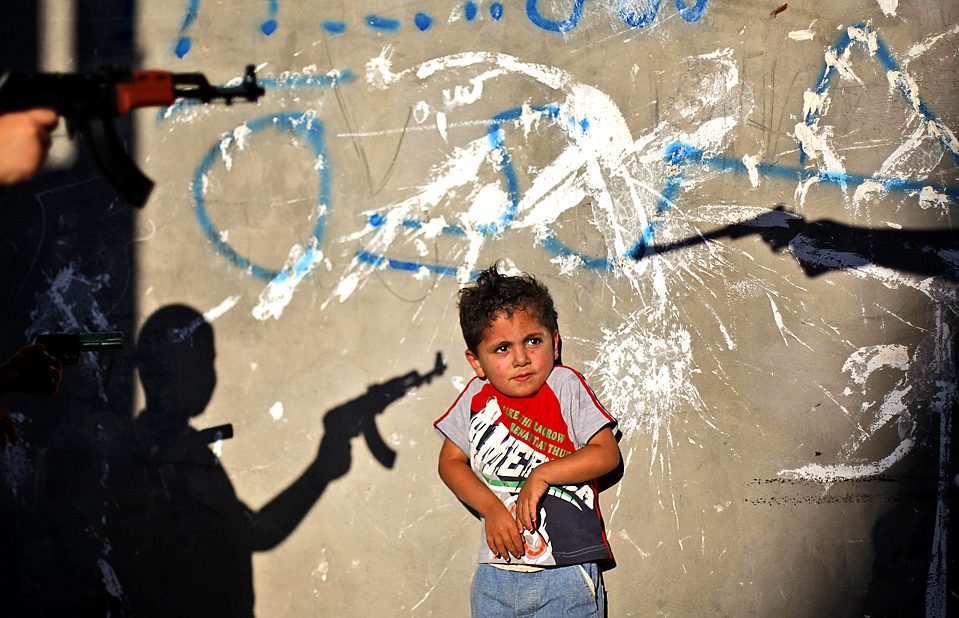 Палестинский мальчик испугался игрушечного оружия во время игры «в войнушки» с подростками в лагере беженцев Аль-Амари на Западном берегу в Рамале. (Muhammed Muheisen/Associated Press)
