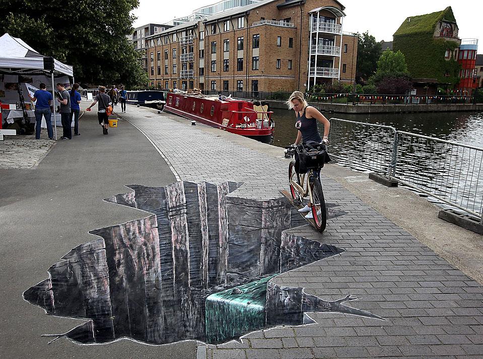 Девушка заглядывает в трехмерный рисунок на пешеходной дорожке, идущей вдоль берега канала Регент в Лондоне. Эта художественная работа –часть компании по безопасному велосипедного движения при движении по пешеходным дорожкам. (Dan Kitwood/Getty Images)