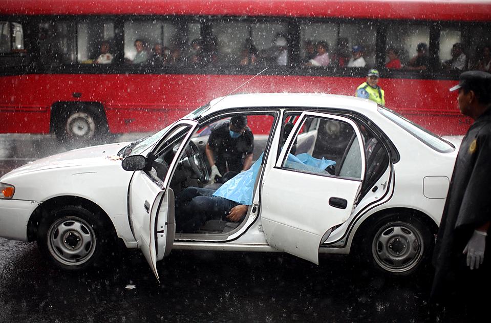 Убитый неизвестными лежит в автомобиле, а вокруг него работают полицейские следователи, Гватемала. (Rodrigo Abd/Associated Press)