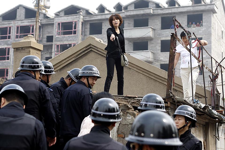 Полицейские снимают с крыши женщин, которые забрались туда в знак протеста против сноса их домов в китайском городе Чанчунь. Китайские власти объявили, что в стране увеличивается напряженность в связи с глобальным финансовым кризисом и приказали силовым структурам соблюдать повышенное внимание. (AFP/Getty Images)