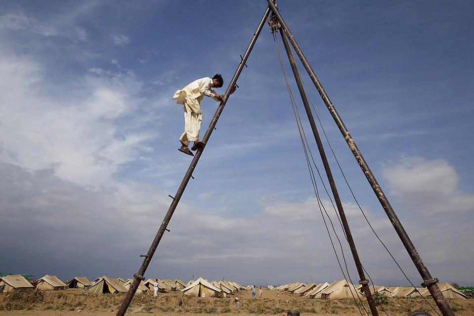 Человек спускается вниз с установки для бурения скважин по добыче питьевой воды в лагере беженцев Чота Лахор в пакистанском городе Сваби. Более трех миллионов беженцев живут сейчас в лагерях вдали от своего дома в результате недавних военных операций против Талибана. (Paula Bronstein/Getty Images)