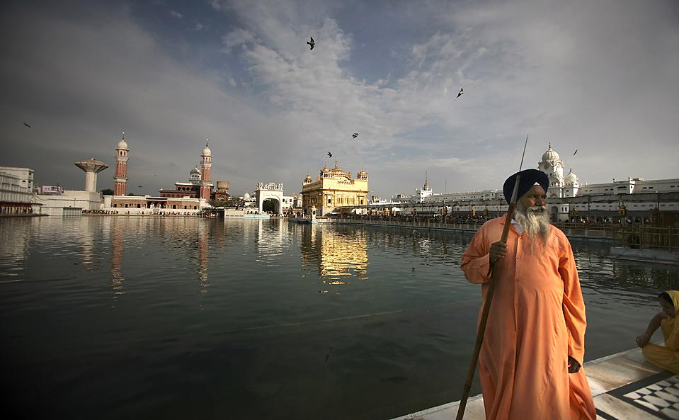 Охранник-сикх с копьем у Золотого Храма в Амритсаре, самого священного святилища сикхов, во время паломничества по случаю чествования пятого сикхского гуру Арджана Сингха, в индийском городе Амритсар. (Altaf Qadri/Associated Press)