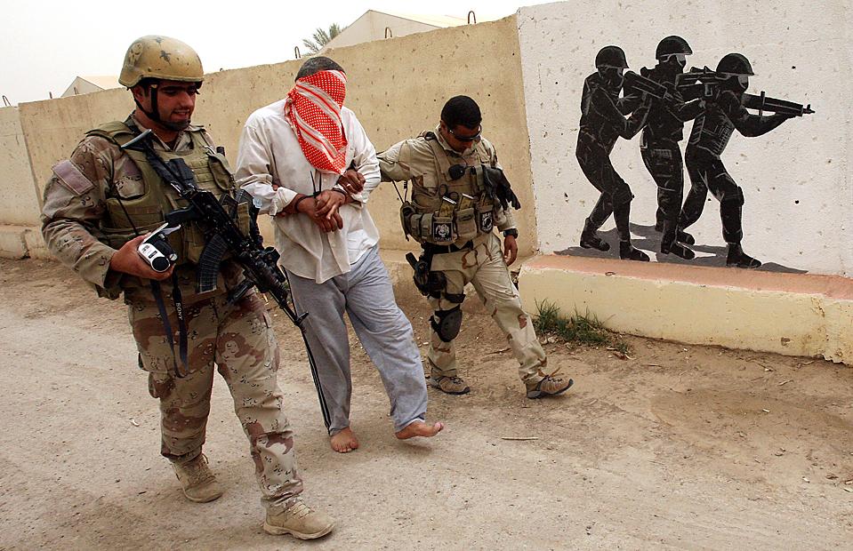 Иракская полиция сопровождает арестованного Ахмеда Абеди, который обвиняется в пособничестве Аль-Кайде и убийстве Харифа Аль Обаиди – мусульманина-суннита, парламентария и защитника прав человека. Хариф Аль Обаиди был застрелен в багдадской мечети на прошлой неделе. (Mohammed Sawaf/AFP/Getty Images)