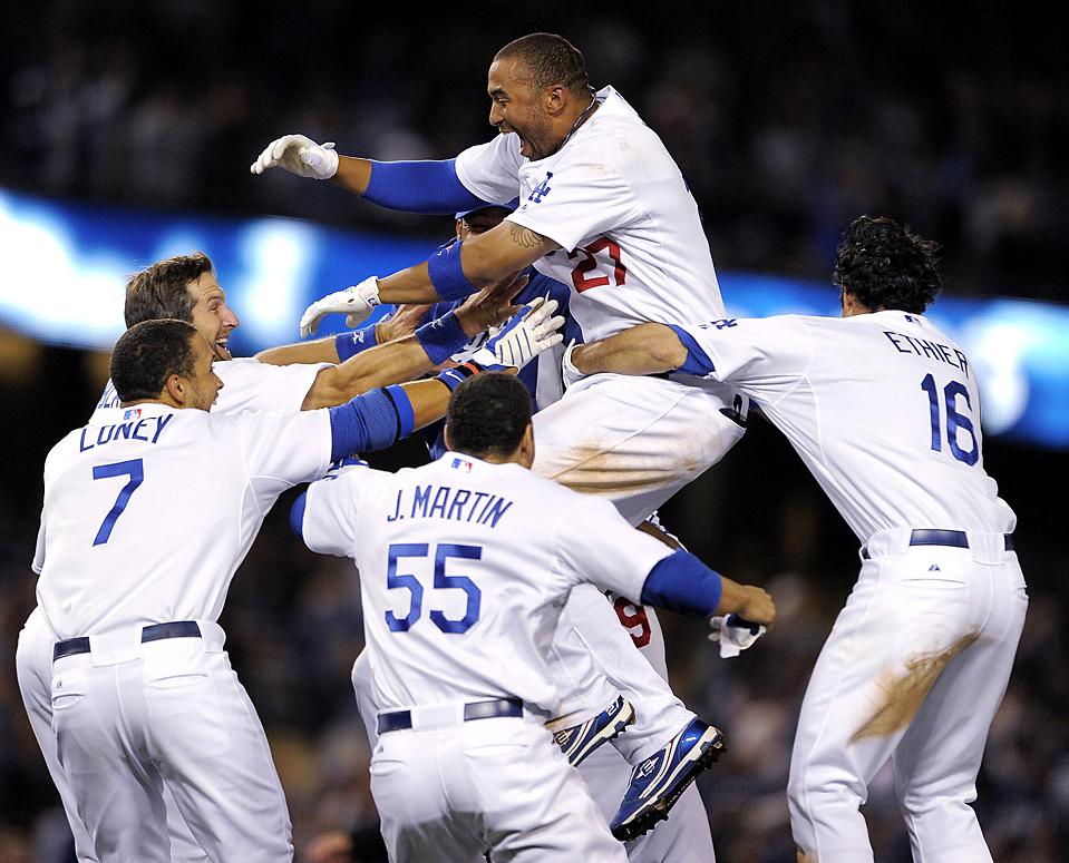 Мэтт Кемп (сверху) из команды Los Angeles Dodgers празднует победу в игре против Oakland Athletics. (Chris Carlson/Associated Press)