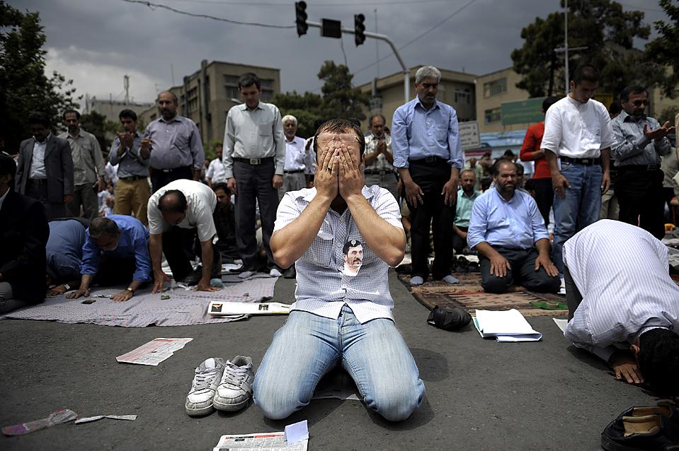 Иранцы молятся после проповеди Верховного лидера аятоллы Али Хаменеи в Тегеранском университете в пятницу. Аятолла призвал прекратить уличные протесты по поводу спорных президентских выборов и признать законным победителем Махмуда Ахмадинежада. (Olivier Laban-Mattei/Agence France-Presse/Getty Images)
