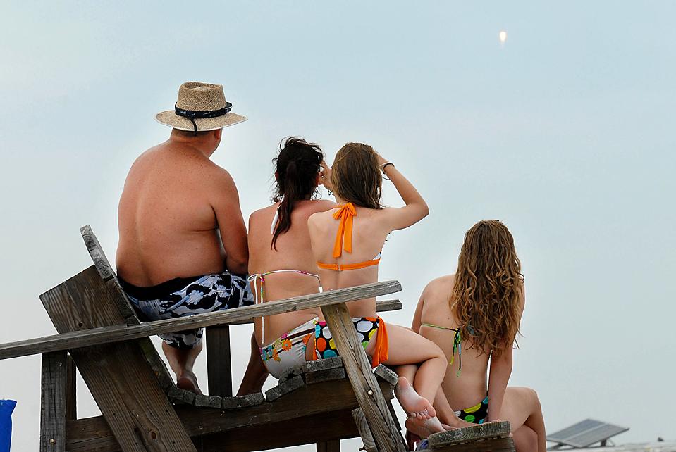 Семейство Пейн наблюдает за взлетом ракеты с пляжа Джетти Парк на мысе Канаверал, штат Флорида в четверг. НАСА надеется, что ракета, перевозящая зонды для исследования поверхности Луны и поиска воды, будет началом большого проекта по возвращению астронавтов на Луну к 2020 году. (Craig Bailey/Florida Today via Associated Press)