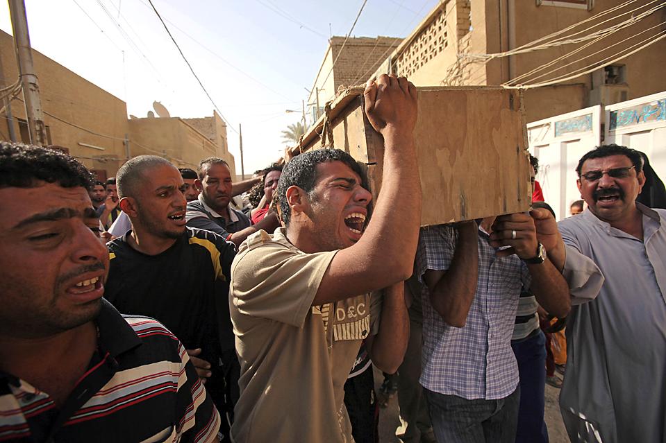 15) Мужчины несут гроб с телом своего родственника, который был убит в среду в результате взрыва бомбы в главном шиитском районе Багдада, в результате которого погибли 78 человек. Бомба разорвалась на многолюдном рынке в среду в Садр-Сити, менее чем за неделю до вывода войск США из городов Ирака. (Karim Kadim/Associated Press)