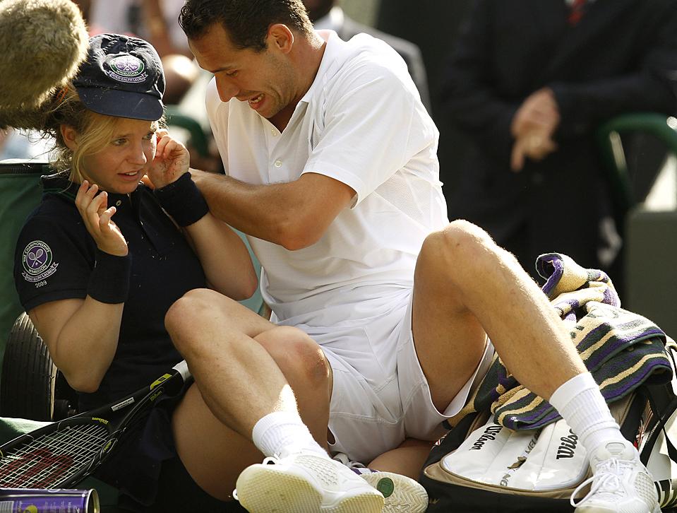 Француз Мишель Ллодра столкнулся с девочкой, которая подает мячи, во время второго раунда игры на Уимблдоне в среду против Томми Хаас из Германии. Ллодра ушибся во время этого инцидента, и покинул матч. (Kirsty Wigglesworth / Associated Press)