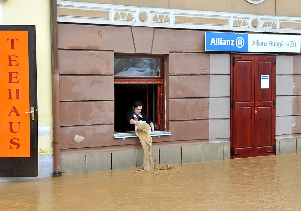 Женщина вычерпывает воду из офиса страховой компании, после того как из-за проливных дождей затопило улицы венгерского города Кёсег, в 200 км к западу от Будапешта. Уровень воды поднялся до полуметра. (Andrea Gerencser/MTI/Associated Press)