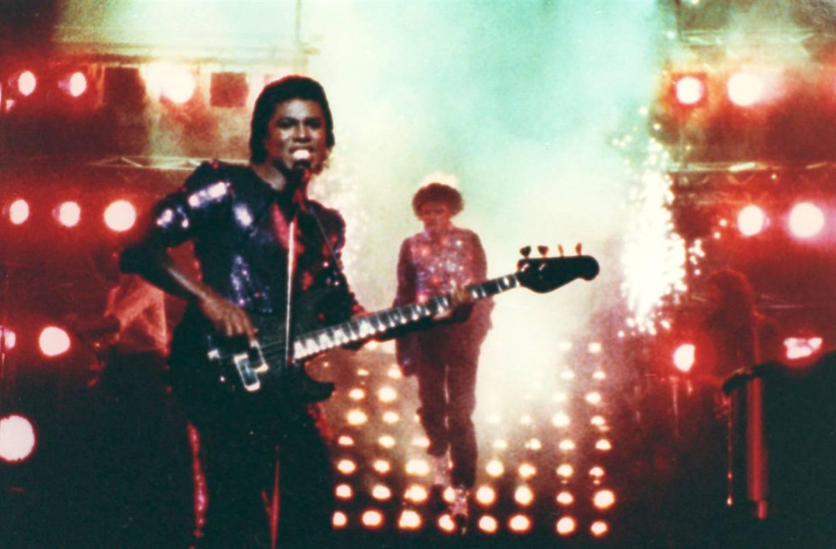 Майкл Джексон (на заднем плане) во время съемок рекламы «Пепси», когда у него загорелись волосы, а его брат Джерман (на переднем плане) продолжает выступать, не зная, что происходит. (AP)