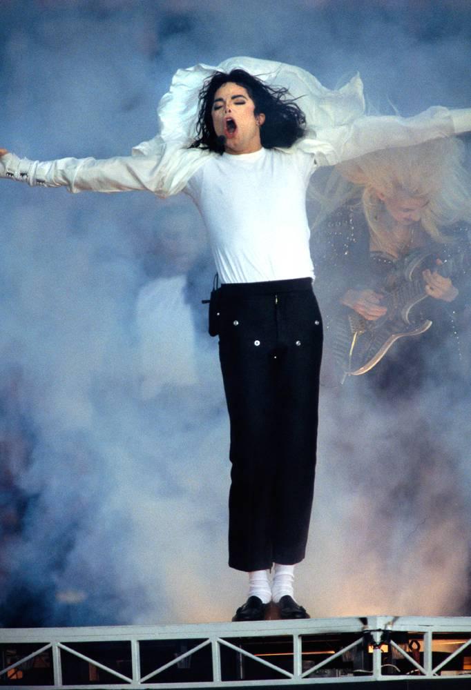 Майкл Джексон выступает перед 30 000 детей на концерте «Super Bowl Half-Time Show» 31 января 1993 году. Несмотря на обвинения в адрес певца, он все равно был на вершине музыкального олимпа, выпустив такие хиты, как «Black or White», «Remember the Time», а его альбом «Dangerous» стал мультиплатиновым. (Ralf-Finn Hestoft/Corbis)