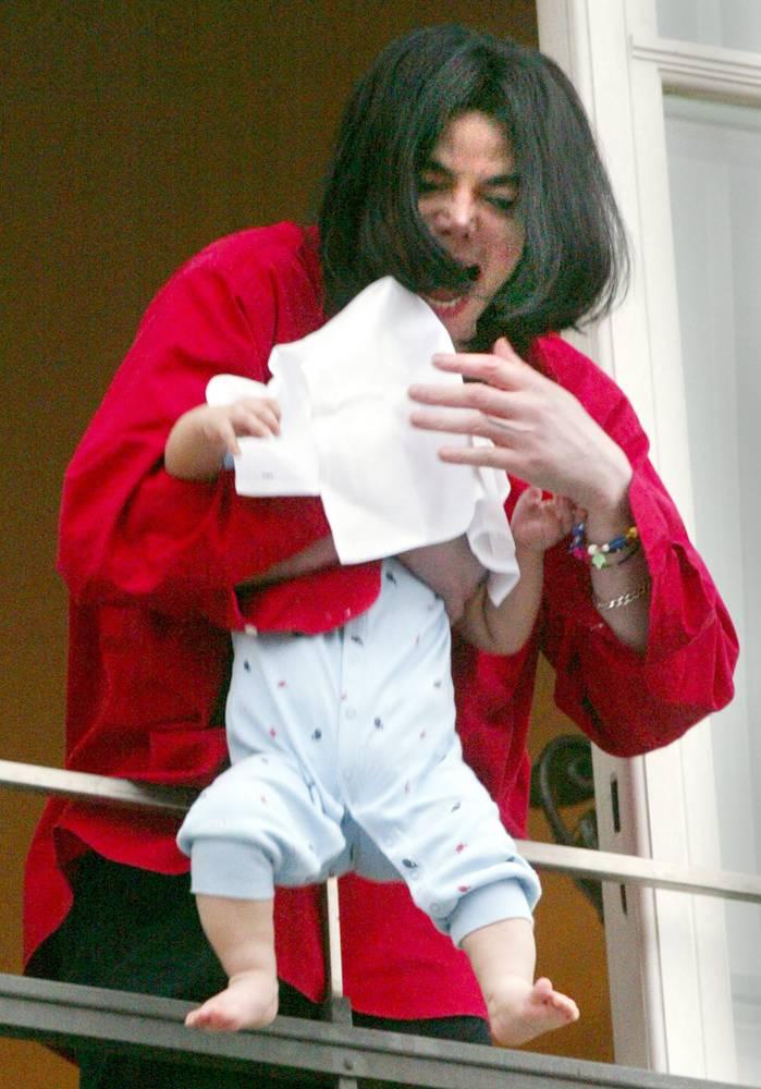 Джексон держит своего сына Принца Майкла II накрытого полотенцем, стоя на балконе берлинской гостиницы 19 ноября 2002 года. Впоследствии Джексон назвал произошедшее «ужасной ошибкой», однако эта фотография потрясла даже самых преданных фанатов певца. Его репутации был нанесен необратимый урон. (Tobias Schwarz/Reuters)