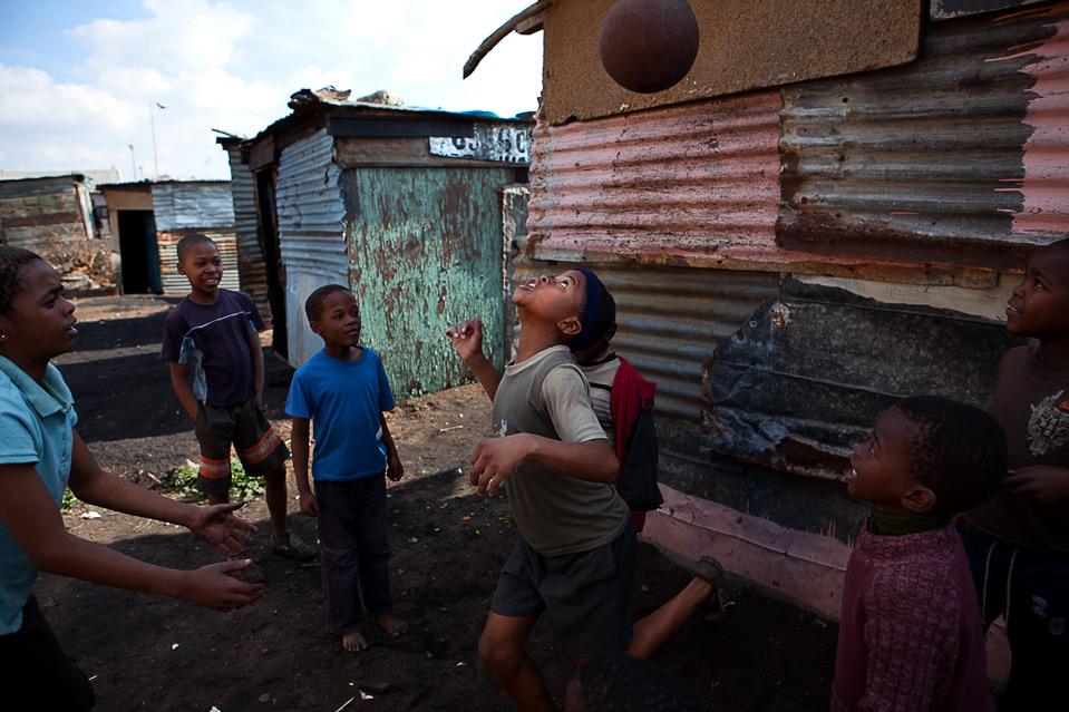 Дети играют в футбол в Соуэто 12 июня, за два дня до начала матча Кубка конфедераций FIFA в Йоханнесбурге. (YASUYOSHI CHIBA/AFP/Getty Images)
