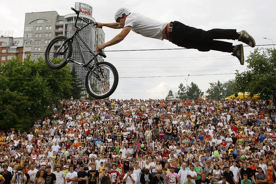 Велоэкстремал Антон Сидоров выполняет трюк во время торжеств по случаю Дня города в Красноярске 12 июня. (REUTERS/Ilya Naymushin)