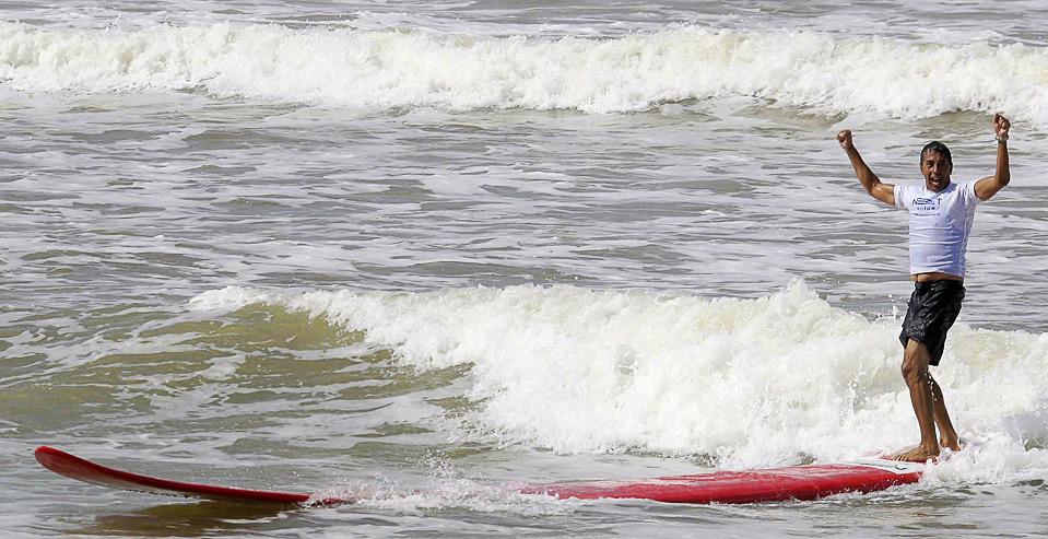 Легендарный бразильский серфингист Рико де Соуза установил Рекорд Гиннеса по езде на самой большой доске для серфинга (31,036 футов или почти 9,5 метров) на пляже Jacaraipe в бразильском городе Серра 12 июня. (REUTERS/Fotocom.net/Marcio Rodrigues/Handout)