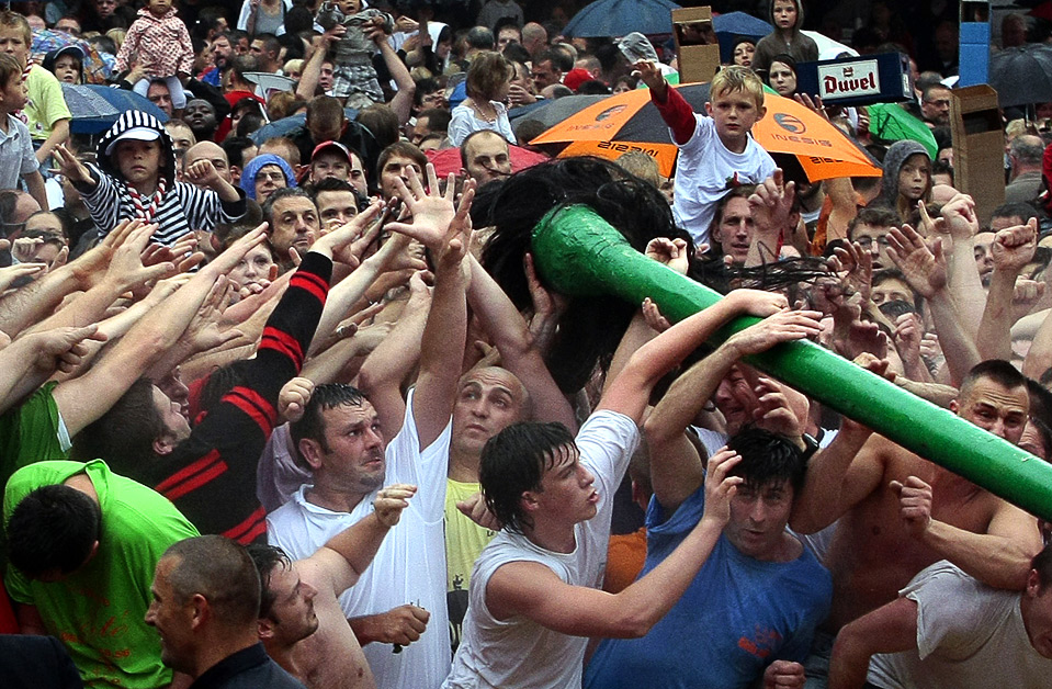Во время традиционного праздника Le Doudou в бельгийском городе Монс люди пытаются выдернуть волосок из «хвоста дракона», который, как считается, приносит удачу в течение всего следующего года. Во время ежегодного празднования разыгрывается битва между Святым Георгием и драконом. (REUTERS/Sebastien Pirlet)