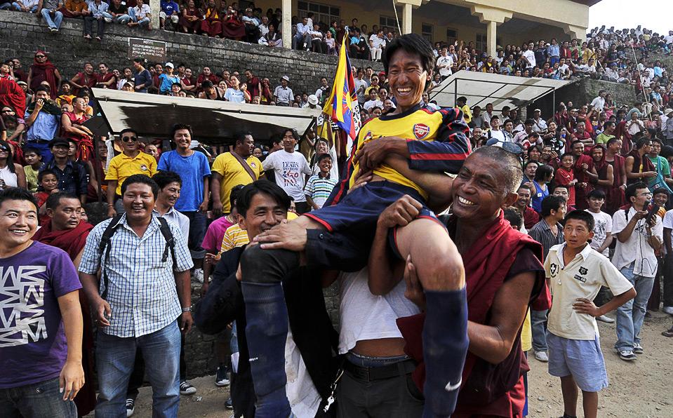 Лобсанга Норбу, футболиста из клуба Potala несут на руках, после того как его команда выиграла Золотой кубок футбольного турнира в индийском городе Dharmsala 9 июня. Клуб Potala стал победителем 10-дневного турнира, в которой участвовали 19 команд тибетских беженцев в Индии и Непале. (AP Photo/Ashwini Bhatia)