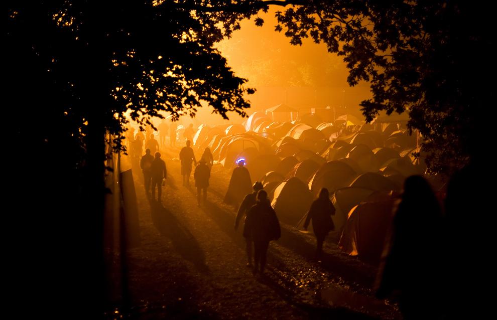 Участники фестиваля идут через кемпинг ранним утром второго дня ежегодного фестиваля Гластонбери близ 27 июня2009. (Leon Neal/AFP/Getty Images)