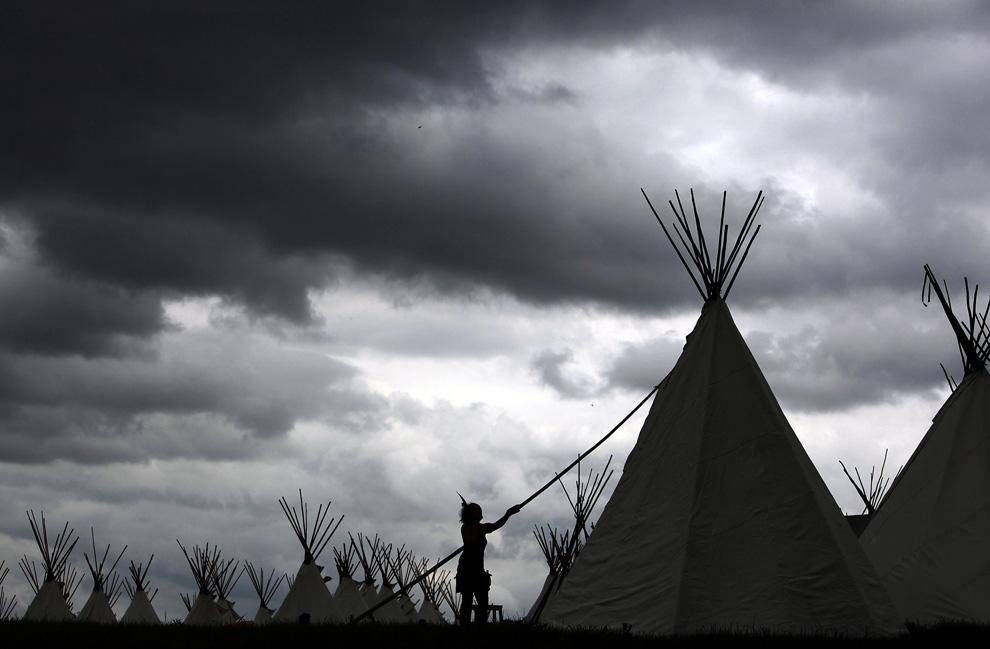 Один из членов персонала устанавливает вигвам в индейском поселке фестиваля Гластонбери 18 июня 2009. Вигвамы, каждый из которых стоил 800 британских фунтов, предназначались для размещения участников фестиваля и были полностью забронированы. (Matt Cardy/Getty Images)
