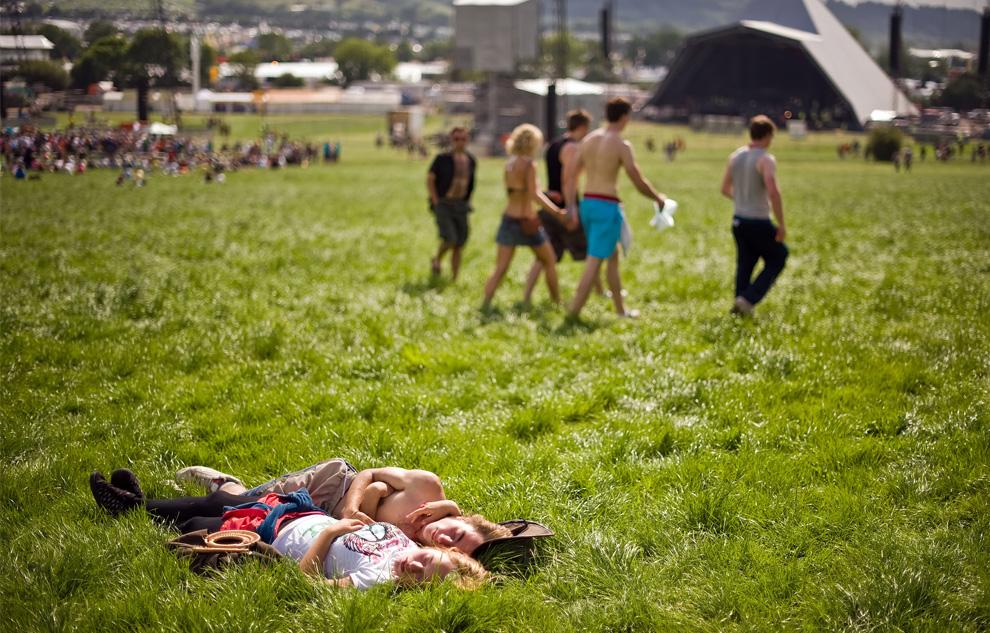 Парочка нежится на солнце в первый день ежегодного фестиваля Гластонбери 24 июня 2009. (Leon Neal/AFP/Getty Images)