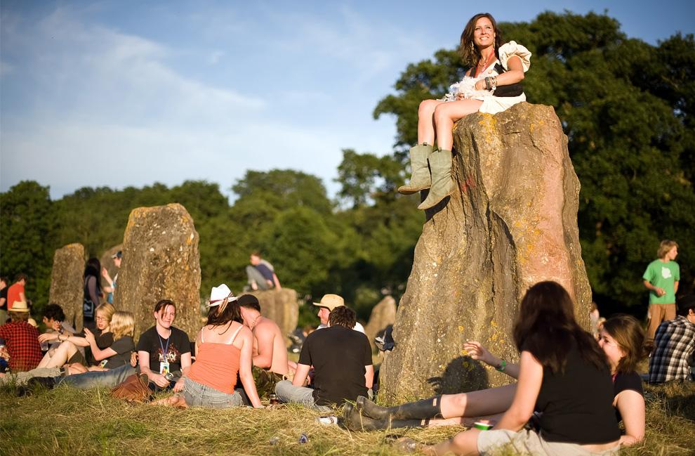 Участники фестиваля отдыхают под лучами вечернего солнца на древних каменных дольменах в первый день фестиваля Гластонбери 24 июня 2009. (Leon Neal/AFP/Getty Images)