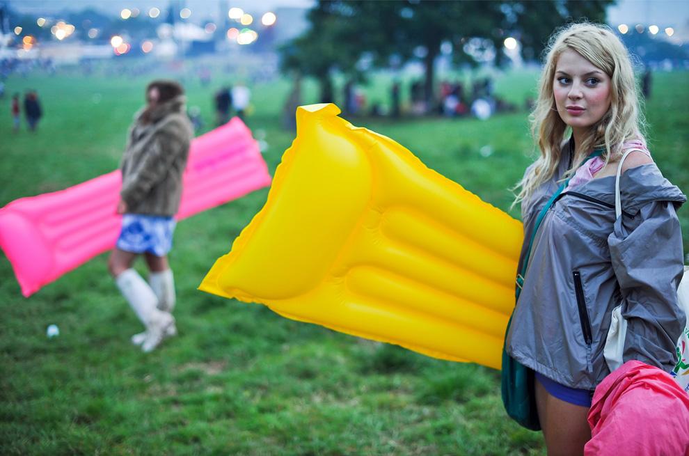 Девушки идут через фестивальную площадку вечером 25 июня 2009, в день официального начала четырехдневного музыкального марафона Glastonbury 2009. (Leon Neal/AFP/Getty Images)