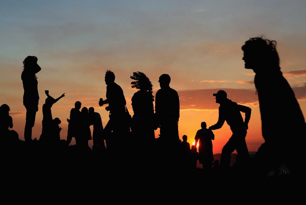 9) Люди собираются, чтобы полюбоваться закатом на холме над полем, где стоят вигвамы, а в это время музыкальные фаны начинают прибывать на фестивальную площадку вечером 24 июня 2009. (Matt Cardy/Getty Images)
