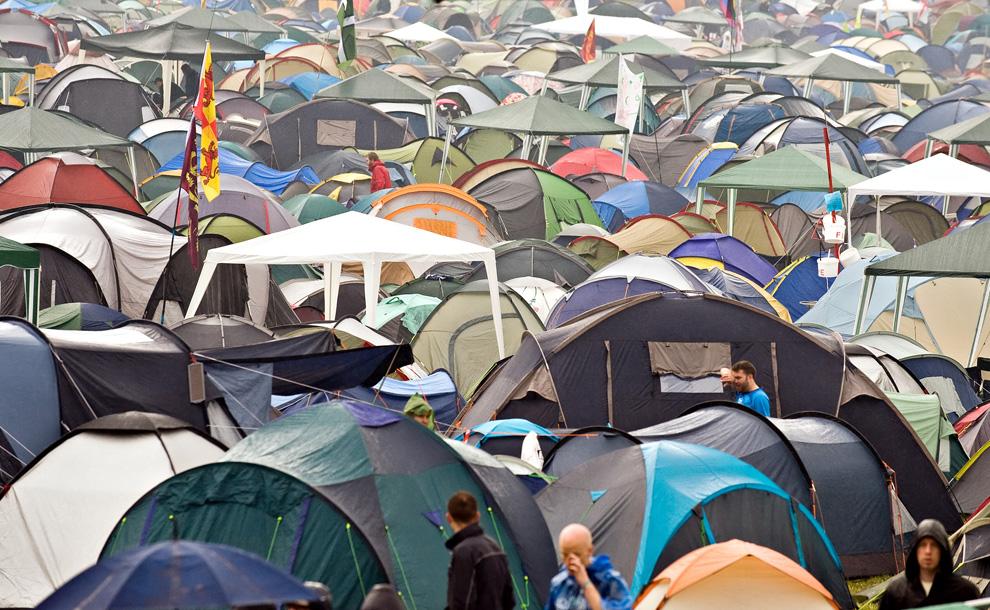 15) Гости фестиваля идут среди мокрых от  дождя палаток в первый день ежегодного фестиваля Гластонбери 26 июня 2009. (Leon Neal/AFP/Getty Images)