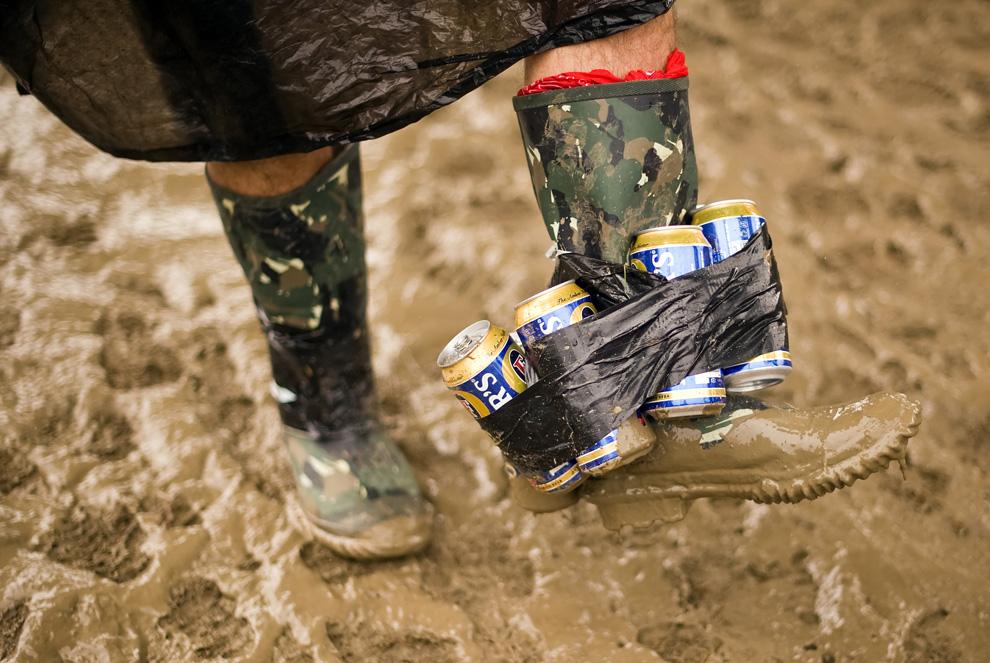 16) Один из гостей фестиваля Гластонбери демонстрирует свои запасы пива 26 июня 2009. (Leon Neal/AFP/Getty Images)