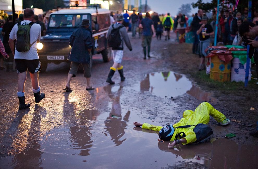18) Некто лежит в грязи вечером накануне первого дня фестиваля в Гластонбери, 25 июня 2009. (Leon Neal/AFP/Getty Images)