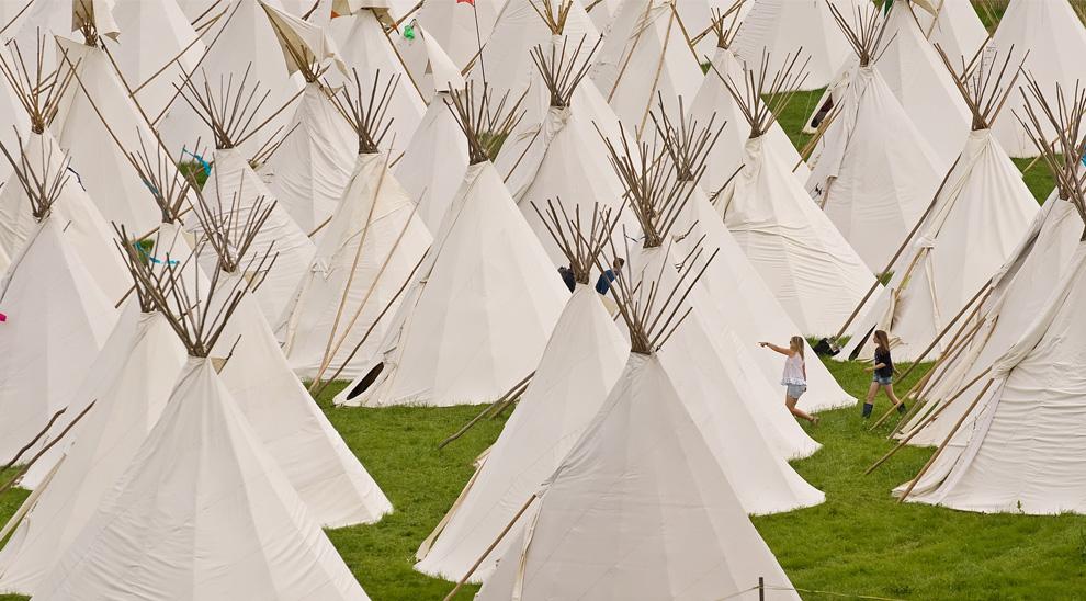 20) Девушки ходят среди типи на второй день фестиваля в Гластонбери по 25 июня 2009. (Leon Neal/AFP/Getty Images)