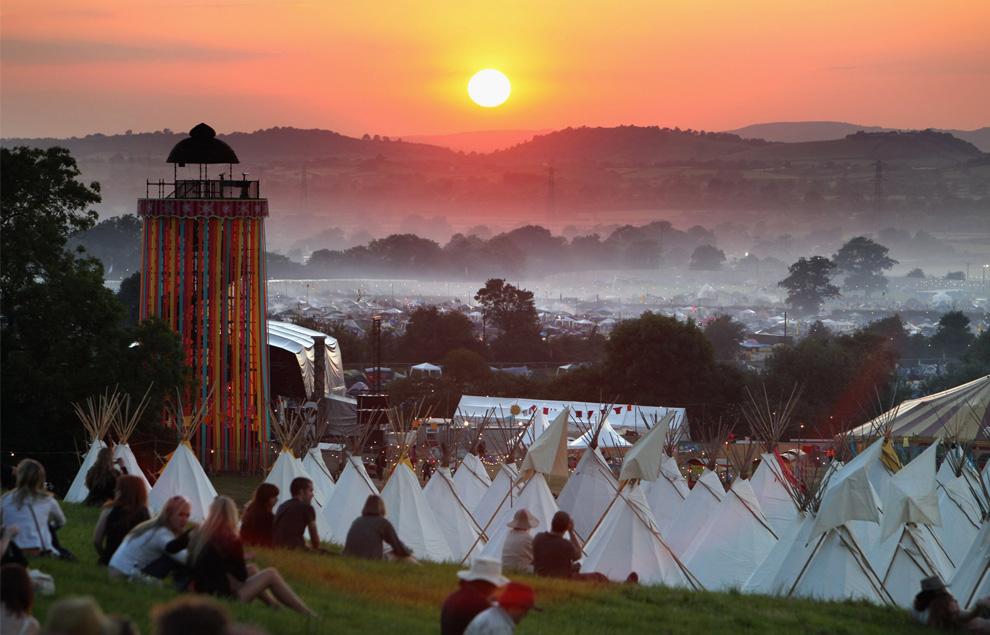 26) Люди собираются, чтобы полюбоваться закатом на холме над полем, где стоят вигвамы, а в это время музыкальные фаны идут через фестивальную площадку вечером 24 июня 2009. (Matt Cardy/Getty Images)