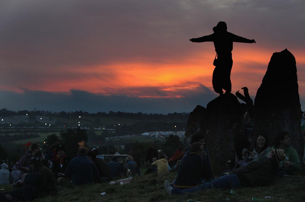 27) Участники фестиваля Гластонбери у каменного круга на рассвете смотрят, будет ли светить солнце. Фото сделано 25 июня 2009 года в Гластонбери, Сомерсет, Англия. (Matt Cardy/Getty Images)