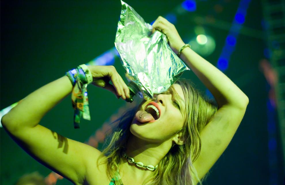 28) Девушка в одном из танцевальных тентов пьет вино из пакета во время выступления французского DJ Missill в первые часы третьего дня фестиваля Гластонбери, 27 июня 2009. (Leon Neal/AFP/Getty Images)