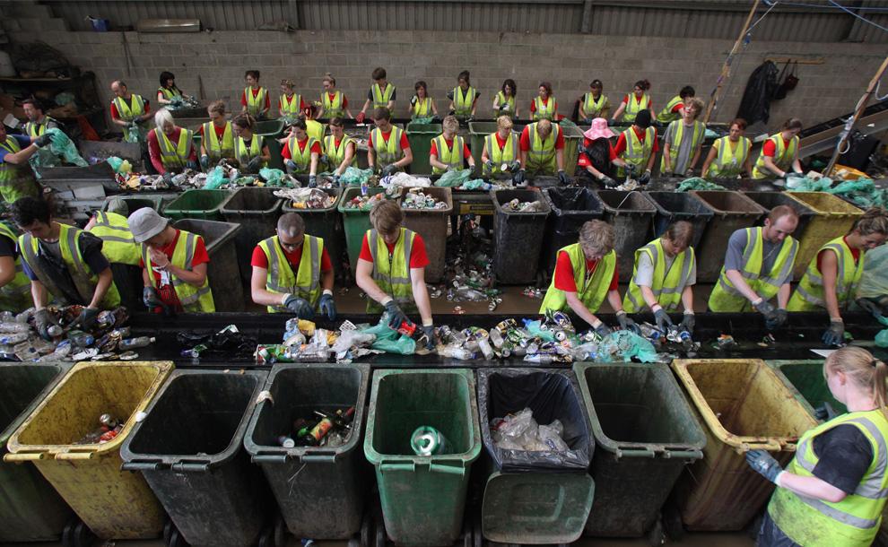 33) Добровольцы сортируют мусор для утилизации в центре вторичной переработки отходов на фестивале Гластонбери 29 июня 2009 года. Каждый год на фестивале работает коллектив из 1200 добровольцев. Люди работают сменами по четыре и шесть часов в счет оплаты билетов на фестиваль: сортируют мусор. А за время проведения фестиваля собирается 2000 тонн отходов. Переработка всех банок, тарелок, стаканов, пластмассы и пищевых отходов, которые остаются после многотысячной толпы, начинается в пятницу и продолжается целую неделю. А полная очистка фестивальной площадки может продолжаться вплоть до августа. (Matt Cardy/Getty Images)