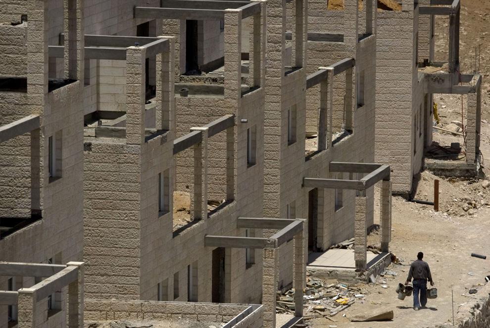 Pekerja Palestina berjalan melalui situs pembangunan sebuah proyek perumahan baru di pemukiman Tepi Barat Yahudi Maale Adumim, dekat Yerusalem, Minggu, 7 Juni, 2009.  (AP Photo / Sebastian Scheiner)