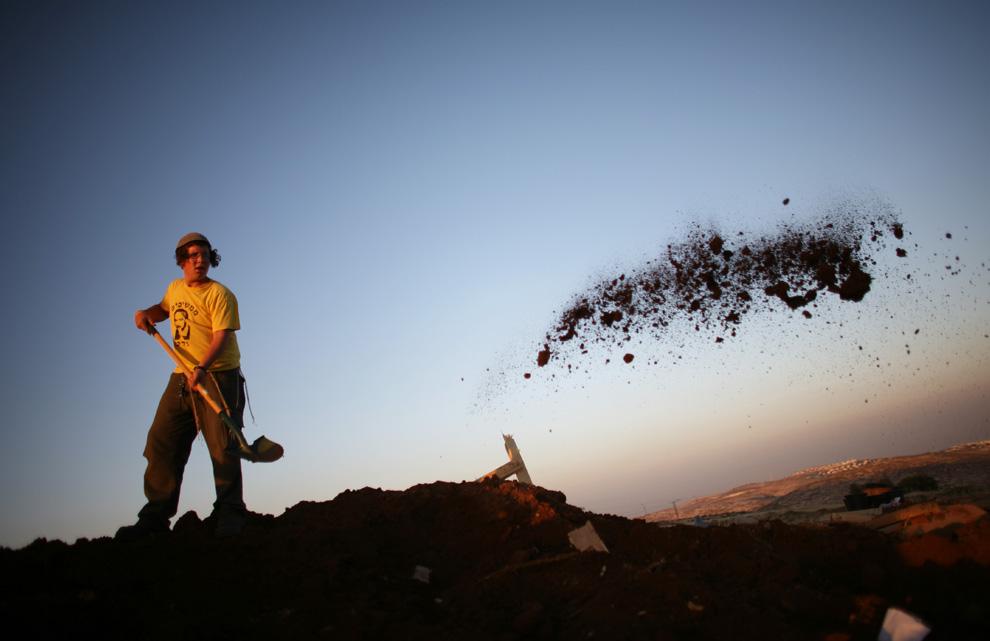 Еврейский поселенец восстанавливает свое поселение после того, как израильские полицейские разрушили его 3 июня 2009 года в Рамат Мигрон, к востоку от Рамаллы. (Uriel Sinai/Getty Images)