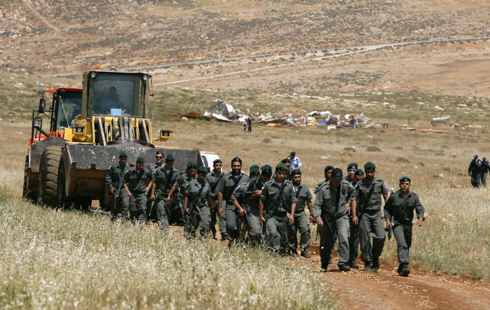 Polisi perbatasan Israel pergi setelah pembongkaran pos Maoz Ester (bagian yang terlihat di latar belakang), dekat pemukiman Yahudi Kochav Hashahar, utara-timur bagian dari kota Tepi Barat Ramallah 21 Mei 2009.  Menurut polisi Israel, penjaga perbatasan hari itu menghancurkan pos tidak sah pemukim di Tepi Barat yang diduduki dan dihancurkan buldoser tujuh tempat tinggal improvisasi.  (REUTERS / Baz Ratner)