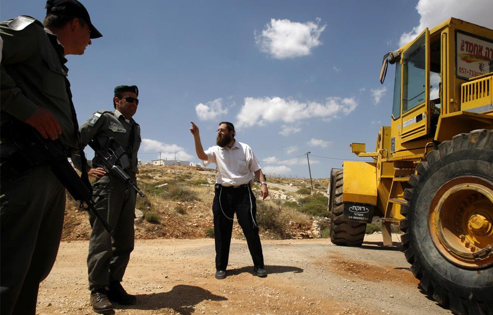 Еврейский поселенец кричит на пограничных полицейских после сноса форпоста Маоц Эстер близ еврейского поселения Кохав Хашахар, к северо-востоку от Рамаллаха, 21 мая 2009. (REUTERS/Baz Ratner)
