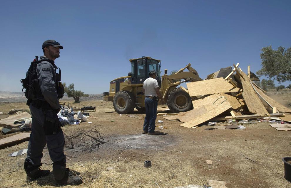 Израильский полицейский наблюдает за тем, как бульдозер сносит импровизированную постройку в несанкционированном поселении Рамат Мигрон, недалеко от расположенного на Западном берегу города Рамаллах 3 июня 2009. (REUTERS/Baz Ratner)