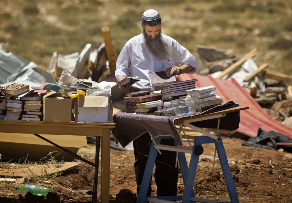 Pemukim Yahudi menganggap doa, yang ditarik dari puing-puing bangunan hancur dihancurkan oleh pasukan Israel di pemukiman ilegal Maoz Ester, pada Rabu, Juni 3, 2009.  (AP Photo / Sebastian Scheiner)