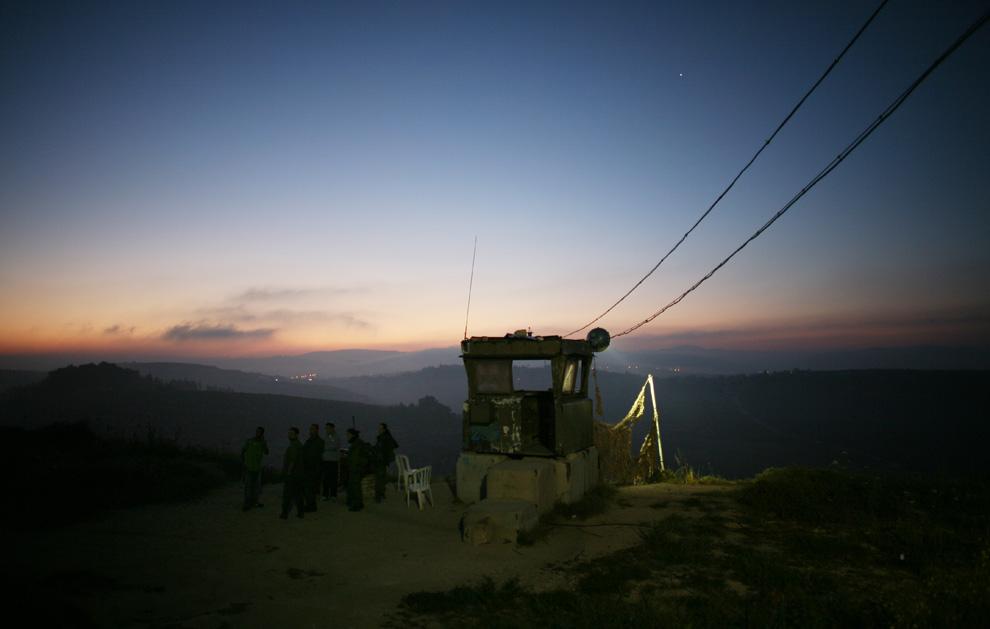 Tak jauh dari pemukiman di kota Tepi Barat Nablus di pemukim Yahudi dan tentara Israel berdiri di menara dalam penyelesaian Ramat Gilad, karena pemukim disiapkan untuk evakuasi kemungkinan polisi Israel di pagi hari, 01 Juni 2009.  Selama serangan itu, pemukim Yahudi pada malam dari beberapa pekerja Palestina terluka dan salah satu dari mereka membutuhkan perawatan rumah sakit, sebagai  mendapat tengkoraknya retak.  Puluhan pemukim bertopeng melempari mobil mereka pekerja Palestina.  (Uriel Sinai / Getty Images)